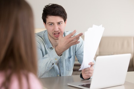 Couple arguing about some papers at home, not able to pay the bills. Husband is angry at wife about credit card statements, waste of money. Business dispute about contracts, paperwork error Imagens