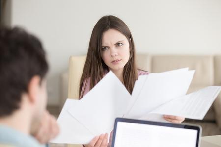 Paar bespreken binnenlandse rekeningen, bankafschriften, vrouw met papieren op zoek boos en gefrustreerd, gevonden fout in onjuiste documenten, contracten, ontevreden vrouwelijke klant praten met manager