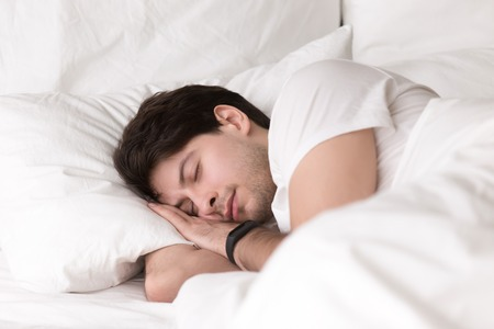 Man is asleep in cozy white bed at night, handsome young guy sleeping at home with wearable electronic device smart watch on his wrist for sleep tracking, monitoring heart rate for healthcare Archivio Fotografico