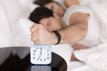 Couple awakened by alarm clock in bed at home, guy lying on bed annoyed by noisy alarm clock in the morning trying to turn it off with his fist, sleeping badly, not enough sleep, hangover or headache