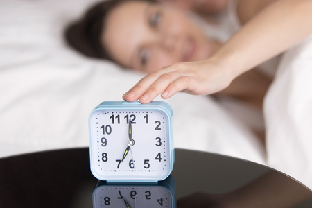 turn table: Rested happy woman reaching clock button to turn off daily alarm signal and wake up. Young couple in bed being woken up in the morning. Focus on hand with clock on the table. Wake-up time