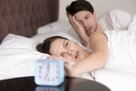 get tired: Young sleepy man and woman trying to turn off annoying loud waking up signal of alarm clock, lying in bed in the morning, feeling bad after sleepless night, having a headache or hangover Stock Photo