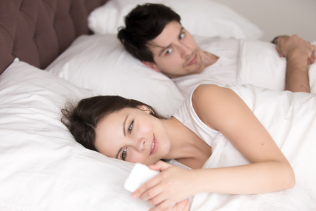 Couple in bed, happy smiling woman turned her back to man, reading message on phone from her lover, worried boyfriend lying next to her, trying to peek at screen. Cheating and infidelity concept