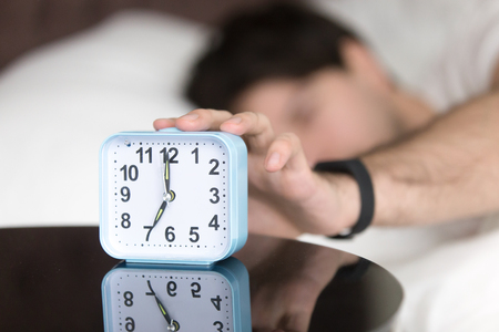 Young man sleeping alone is woken by alarm clock signal in the morning. Awaking guy trying to turn off ringing alarm by the hand still lying in bed at home. Daily alarm telling its time to get up Stock Photo