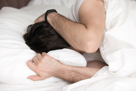 Young guy in bed lying on pillow covering his head and ears with hands as he does not want to wake up, suffering from noisy alarm in the morning or sleep disorder, having a headache or depressed