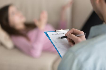 Sluit omhoog van het mannelijke klembord van de psychotherapisholding, vullende informatie over patiënt terwijl dame liggend op laag op de achtergrond, arts die nota's in medische kaart van vrouw in psychologenbureau maken Stockfoto - 76070331