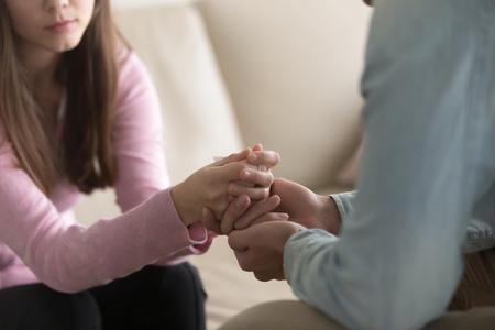 Close-up van overstuur paar, kerel, hand in hand van huilende vrouw, probeert te troosten en haar te troosten, vriend verontschuldigen beledigde dame, om vergeving te vragen. Ondersteuning, spijt en medeleven Stockfoto
