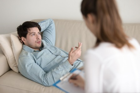 confide: Female psychologist working with young man lying comfortably on couch and talking about his problems. Guy on reception at psychotherapist office, trying to relax and describe his feelings
