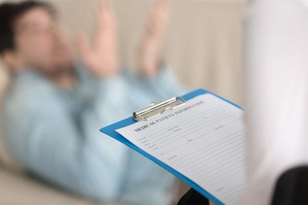 Jonge man bij de receptie bij de psychotherapeut. Focus op Klembord met medische patiëntenkaart in arts hand. Het invullen van persoonlijke informatie over nieuwe patiënten in de kliniek. Gezondheidszorg en behandeling. Detailopname Stockfoto
