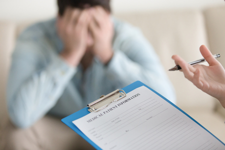 Depressed guy visiting doctor, having complaints about health or mental problems. Focus on doctors hand holding clipboard with patient card, psychologist starts working with troubled man. Close up