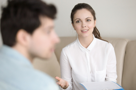 Young female psychotherapist wearing white shirt encouraging and cheering up frustrated male patient, suffering from depression, looking indifferent. Psychological counseling of woman-therapist Stock Photo