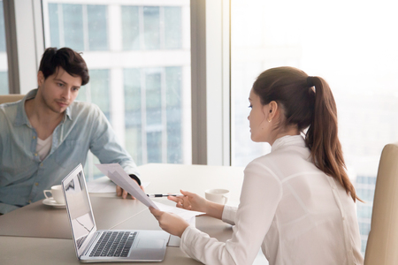 Businessman and businesswoman discussing business issues using laptop and looking through papers. Young woman showing documents to male colleague, man is serious and thinking how to solve a problem Stock Photo