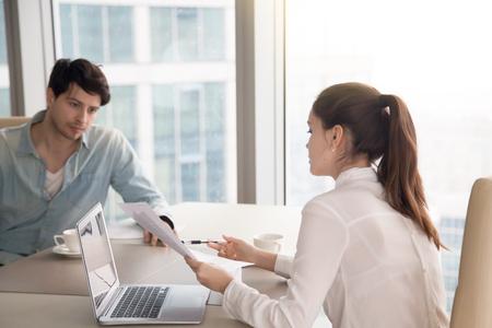 Zakenman en onderneemster die bedrijfskwesties bespreken die laptop met behulp van en door documenten kijken. De jonge vrouw die documenten toont aan mannelijke collega, is de mens ernstig en denkend hoe te om een probleem op te lossen Stockfoto