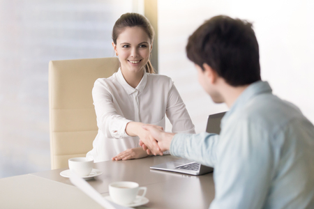 Cheerful businesswoman handshaking with client closing deal in the office, successful candidate get a job after interview, young ambitious female boss greeting client or business partner