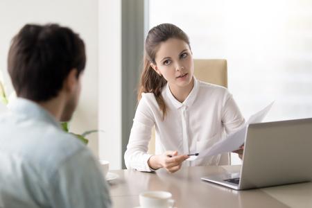 Jonge vrouwelijke baas in gesprek met werknemer, wijzend naar een document, zakenvrouw discussiëren over documenten met partner, hr manager bedrijf sollicitatiegesprek vragen mannelijke kandidaat over werkervaring Stockfoto