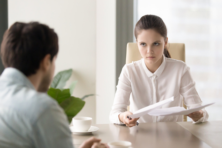 Young business lady holding papers looking at a man with anger, female boss found a mistake in documentation and demanding explanation, male manager can be fired because of his paperwork failure Stock Photo