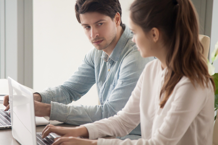 Young male and female rival coworkers sitting together at the office desk using laptops looking in the eye, expressing instant dislike, hate or envy, showing jealousy of other people s success Banque d'images