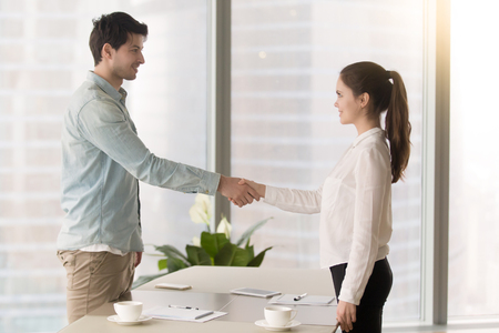 recently: Friendly male executive standing at the office table shaking hands and congratulating recently hired young female manager, greeting or finishing meeting, closing deal or making agreement