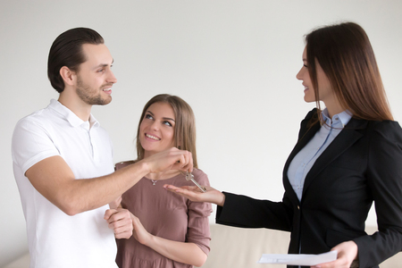 Portrait of female real estate agent handing over keys to cheerful young family property owners just bought new apartment. Happy couple getting house key from realtor, man is proud and taking it