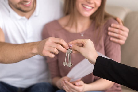 taking a wife: Close up of happy couple getting keys to their new house, hand of a female real estate agent giving apartment keys to a man sitting on sofa embracing his girlfriend, renting or buying home concept