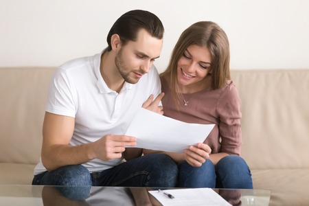 Smiling couple holding papers and carefully studying documents sitting on sofa indoors, reading terms and conditions, reviewing agreement, considering mortgage loan offer, personal insurance Stock Photo