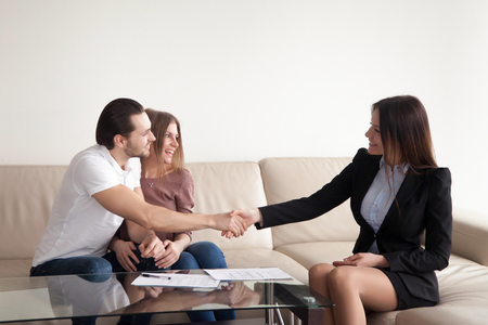 Loving young couple shaking hands with friendly real estate agent, satisfied clients and female manager handshaking, bank loan approved, personal insurance, lease agreement, mortgage investment