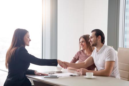 Giovani coppie prosperose che si incontrano con il mediatore femminile nell'agenzia immobiliare. L'uomo e l'agente immobiliare si stringono la mano, felici di fare un affare di acquisto di proprietà, consulente per gli investimenti congratulandosi con i clienti Archivio Fotografico - 76765642