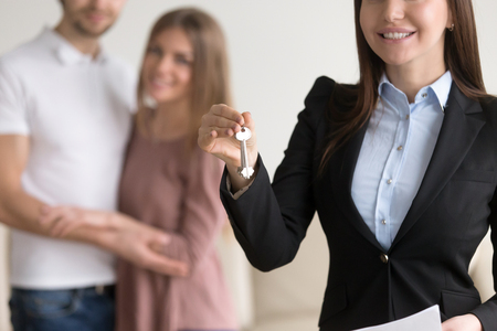 Close up of female real estate agent with keys in focus and hugging young family just bought new home in the background. Real estate market concept, affordable mortgage, first property investment