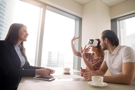 Jonge vrouw die virtuele werkelijkheid bril of bril draagt, paar met behulp van een hoofdscherm voor onroerendgoedreizen, opgewonden door deelname effect, ontdek vrijwel nieuw appartement, koop en verkoop huizen in VR