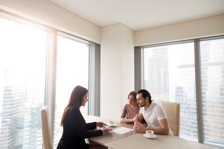 Young family couple meeting with bank worker to sign loan contract, discussing banking credit, personal insurance or mortgage investment, manager showing clients build project on tablet Standard-Bild