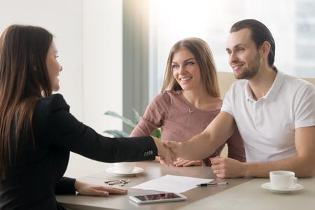 Ontmoeting met agent op kantoor, kopen van appartement of huis huren, kopers van onroerend goed klaar om een deal te sluiten, familiepaar handen schudden met makelaar na ondertekening van documenten voor onroerend goed aankoop
