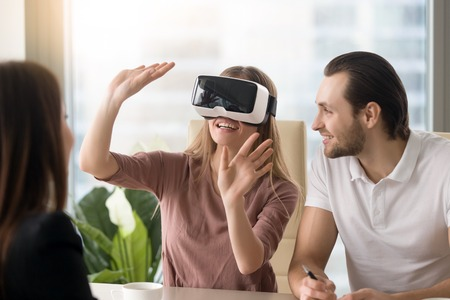 Business team of three people working on virtual reality applications and games, young excited woman testing VR glasses or goggles sitting in the office room with two colleagues, teleconference