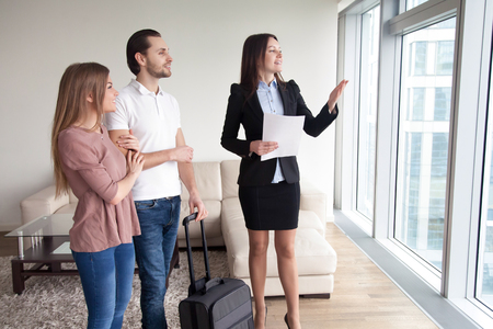 Happy young couple travelers moving in new rented own apartment, standing by the window enjoying view, meeting with female real estate agent showing flat for rent, telling about nearby attractions Stock Photo