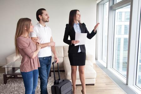 Los viajeros felices de la pareja joven que se mueven en el nuevo piso alquilado propio, de pie junto a la ventana que disfruta de la vista, que se encuentran con el agente inmobiliario femenino que muestra el plano en alquiler, contando sobre atracciones próximas Foto de archivo - 76765681