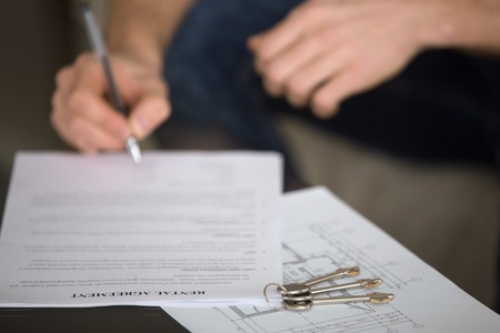 Close up of male tenant signing rental agreement, renter with a pen putting signature, focus on document and keys, young guy or student decided live separately and found home for rent
