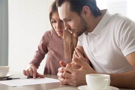 Serious couple studying contract agreement, reading terms and conditions attentively before signing, husband and wife calculating domestic bills, considering mortgage loan offer, health insurance Фото со стока
