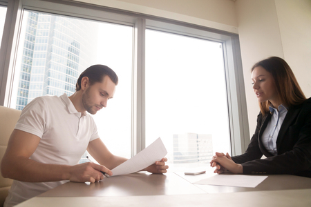 clarifying: Female company director explaining to new employee terms of working contract, assignment to a position. Manager offering customer to sign papers, male client clarifying details of a deal Stock Photo