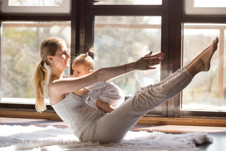 Young yogi happy mother working out, sitting in boat balance pose, wearing white sportswear,  baby on her tummy, fitness at home when having no time for gym, postnatal yoga. Healthy lifestyle concept Фото со стока