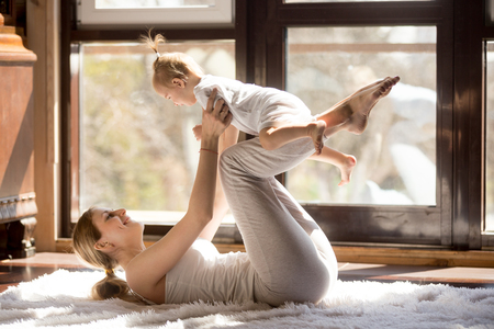 Young mother working out wearing white sportswear,  exercising at home with baby daughter, leg lifting with kid as a weigh, exercising and bonding with child, enjoyment. Healthy lifestyle concept