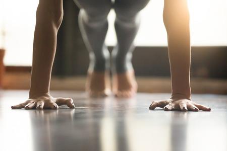 Jonge vrouw het beoefenen van yoga, doet push ups of druk ups oefening, phalankasana Plank pose, het uitwerken, het dragen van kleding, grijze broek, indoor, interieur, vloer van de woonkamer. Close-up van de handen
