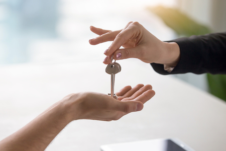 Makelaar in onroerend goed die sleutels geeft aan appartementseigenaar, die een verkoop van onroerend goed bedrijf koopt. Sluit omhoog van mannelijke hand die huissleutel van makelaar in onroerend goed neemt. Hypotheek voor de aanschaf van een appartement, toegang krijgen tot een eigen woning Stockfoto