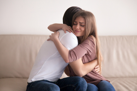 embracement: Portrait of emotional young couple hugging each other tightly, boyfriend and girlfriend embracing sitting on couch, reconciliation after argument, love you so much, strong affection in relationships