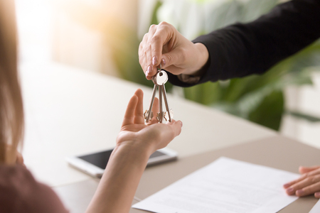 Young lady taking keys from female real estate agent during meeting after signing rental lease contract or sale purchase agreement. Independent woman purchasing new home, close up view Standard-Bild