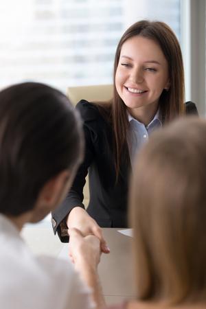 Piękny przyjazny agenta nieruchomości i klienta uzgadniania w biurze, miło cię poznać, businesswoman spotkanie partnerów, drżenie rąk nad stołem, zawieranie umów lub partnerstwa, znajomość firmy Zdjęcie Seryjne