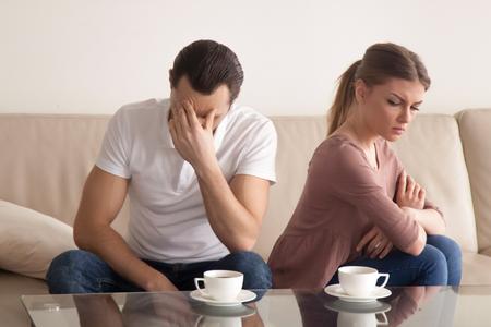 引数の後話ではないソファに座って家族カップル、若い夫は定数口論に疲れていると腕を組んで彼氏に背を向けた彼の額、気分を害する女性に触れ 写真素材
