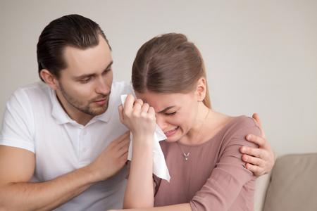 남편이 우울한 아내를 위로하고, 힘든 상황을 지원하고, 동정심을 포옹하는 여자 친구를 위로하기 위해 노력하는 사랑하는 남자 친구, 손수건으로 눈