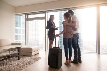 Female real estate agent showing property to young interested couple travellers, just arrived with baggage, tenants moving in or out rented apartment, renting flat on trip, daily rent abroad Imagens