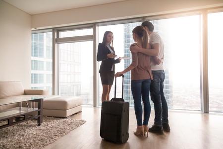 Vrouwelijke makelaar in onroerend goed met onroerend goed aan jonge geïnteresseerde stelreizigers, net aangekomen met bagage, huurders die in of uit een gehuurd appartement verhuizen, flatverhuur op reis, dagelijkse huur in het buitenland Stockfoto