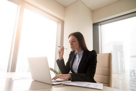 Young serious self-made businesswoman working at office desk on laptop, looking at screen, diagrams on table. Female boss thinking over business project, calculating income and preparing presentation