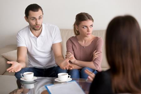 一定の争いと、心理学者との結婚に悩みを議論する夫の心理学者のソファの上の若い家族カップル、黙って座って腹妻武器とよそ見交差 写真素材